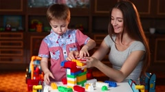 Mom and Her Son Build a House Out of Colored Blocks Stock Footage
