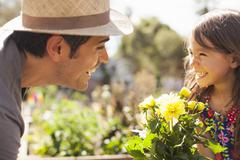 Mid adult man and daughter with yellow flower plant in community garden - stock photo