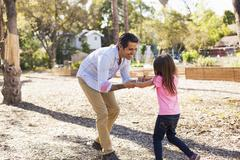 Girl and father playing in community garden Stock Photos
