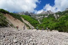 Five mature hikers hiking in valley, Grigna, Lecco, Lombardy, Italy - stock photo