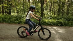 Little girl rides her bike on a forest trail Stock Footage