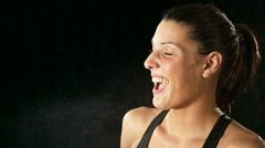 Athletic laughing woman wearing sporstwear is joking around with water Stock Footage