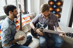 Male couple at home, play guitar and banjo, laughing Kuvituskuvat