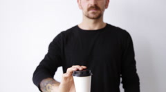 Handsome bearded unfocused guy shows paper cup on camera - stock footage