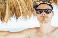 Portrait of mid adult man under cabana, wearing cap and sunglasses, Miami Beach, Stock Photos