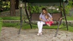 Mother reading a book to children sitting in the Park Stock Footage