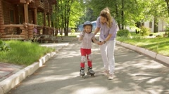 Mom teaches little daughter to roller skate in the Park Stock Footage