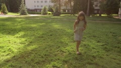 Little girl running on the grass in the Park under the water spray Stock Footage