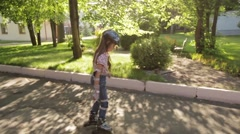 little girl learns to roller skate in the Park - stock footage