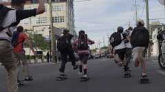 Big group of skateboarders pushing down the street together in slow motion Stock Footage