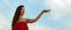 Lady in Red Dress Pouring out Sand from her Hand in a  Desert in Slow Motion Stock Footage