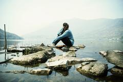 Young woman sitting on rock looking out over Lake Mergozzo, Verbania, Piemonte, - stock photo