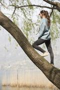 Young woman standing in tree looking out over lake Mergozzo, Verbania, Piemonte, - stock photo