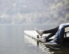 Legs of young couple dangling from pier at Lake Mergozzo, Verbania, Piemonte, - stock photo