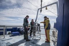 Scientists assembling sea water sampling experiment on research ship Stock Photos