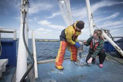 Marine biologists taking samples from plankton net on research ship - stock photo