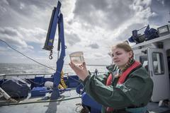 Female scientist inspecting sample of plankton on research ship Stock Photos
