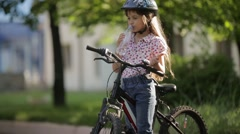Little girl drinks water while standing on the bike Stock Footage