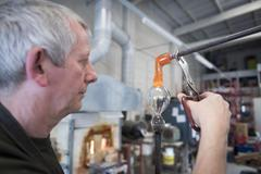 Glassblower adding molten glass stem to glass Stock Photos