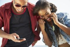 Young couple standing together side by side smiling using smartphone Stock Photos