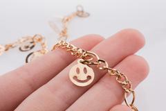 Smileys on a chain in hand Stock Photos