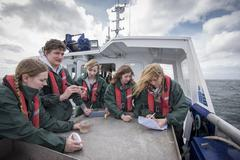Marine biologists students inspecting plankton samples on research ship Stock Photos
