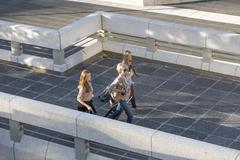 Three adult women walking across elevated walkway - stock photo