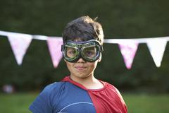 Portrait of boy wearing goggles and cape, looking at camera Stock Photos