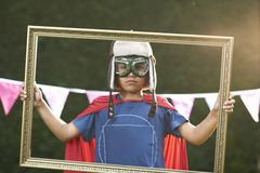 Portrait of boy looking through picture frame wearing cape, goggles and flying Stock Photos