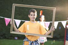 Portrait of boy looking through picture frame, looking at camera Stock Photos
