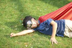 Boy wearing goggles and cape lying on side on grass, flying stance Stock Photos