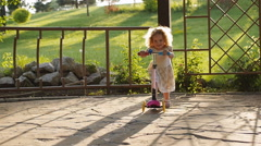 cute curly little girl riding scooter in summer park - stock footage