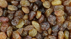 Raisins close up. Loop rotation. Front of the camera rotates plate with raisins Stock Footage