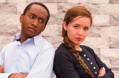 Charming interracial couple posing with upset facial expressions, rubbing - stock photo