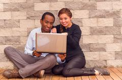 Charming young interracial couple sitting by brick wall with laptop interacting - stock photo