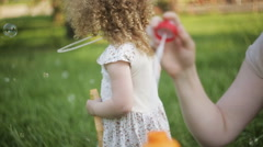 Mother and daughter blowing bubbles outdoors in summer sunshine - stock footage