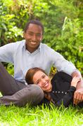 Beautiful young interracial couple in sitting garden environment, embracing and - stock photo