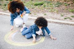 Mother and daughter using chalk to draw colourful circle on pathway - stock photo