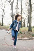 Girl standing on one leg, playing with skipping rope, looking up Stock Photos