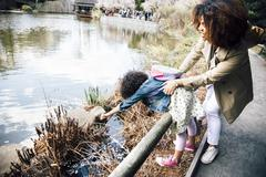 Mother gripping daughter stretching over guard rail to touch plant Stock Photos