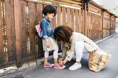 Mother kneeling by fence tying daughters shoelace Stock Photos