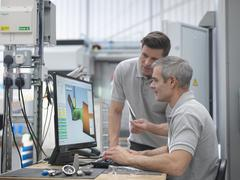 Engineers watching CNC lathe progress on screen in orthopaedic factory Stock Photos