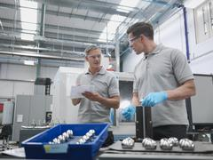 Engineers finishing artificial hip joints in orthopaedic factory - stock photo
