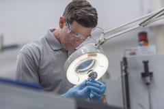 Engineer inspecting artificial hip joint in orthopaedic factory - stock photo