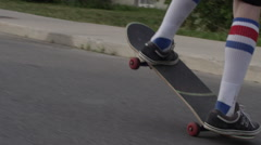 Young skateboarder riding down the street doing a wheelie or manual Stock Footage