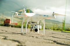 White drone with camera mounted underneath sitting on concrete surface, mountain Stock Photos