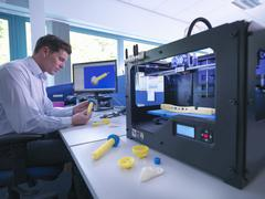 Medical product designer with 3D printing machine with CAD design on screen in Stock Photos