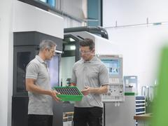 Engineers discussing machined products in orthopaedic factory - stock photo
