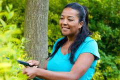 Mature woman pruning hedge in garden - stock photo