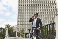 Mid adult business man holding bicycle, making telephone call using smartphone, Kuvituskuvat